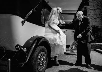 Imperial viscount Landaulette vintage wedding cars liverpool Merseyside UK driver helping bride out of the car west tower aughton wedding venue liverpool merseyside uk